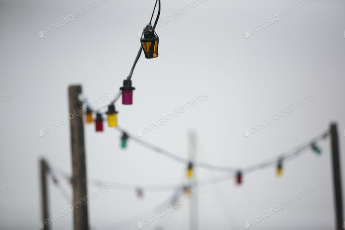 A multicoloured string of electric lights against a grey sky.