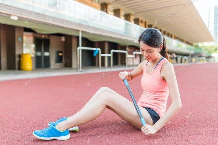 Женщина, использующая роликовую палку для облегчения мышечной боли