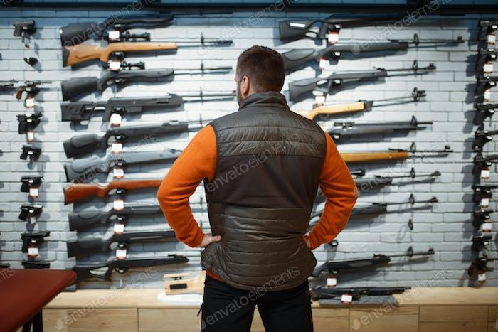 Man at showcase with rifles, back view, gun shop