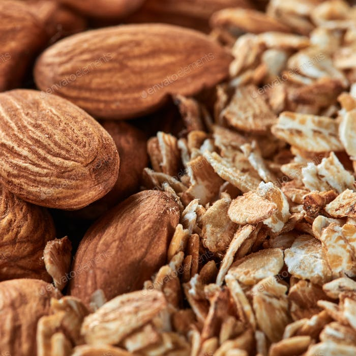 Uncooked oat flakes and almond nuts background. Close up, top view of organic natural product
