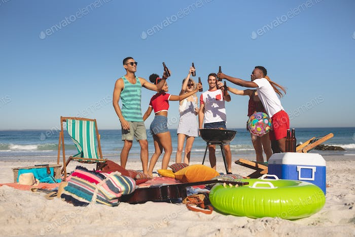 Front view of group of happy diverse friends toasting beer bottles on the beach