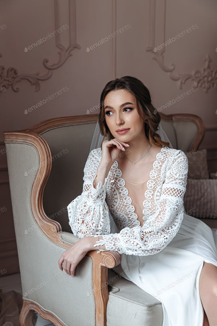 Portrait of a young bride in a chair in a beautiful lace dress.