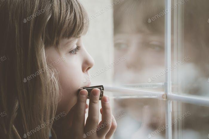 Sad girl playing harmonica by the window