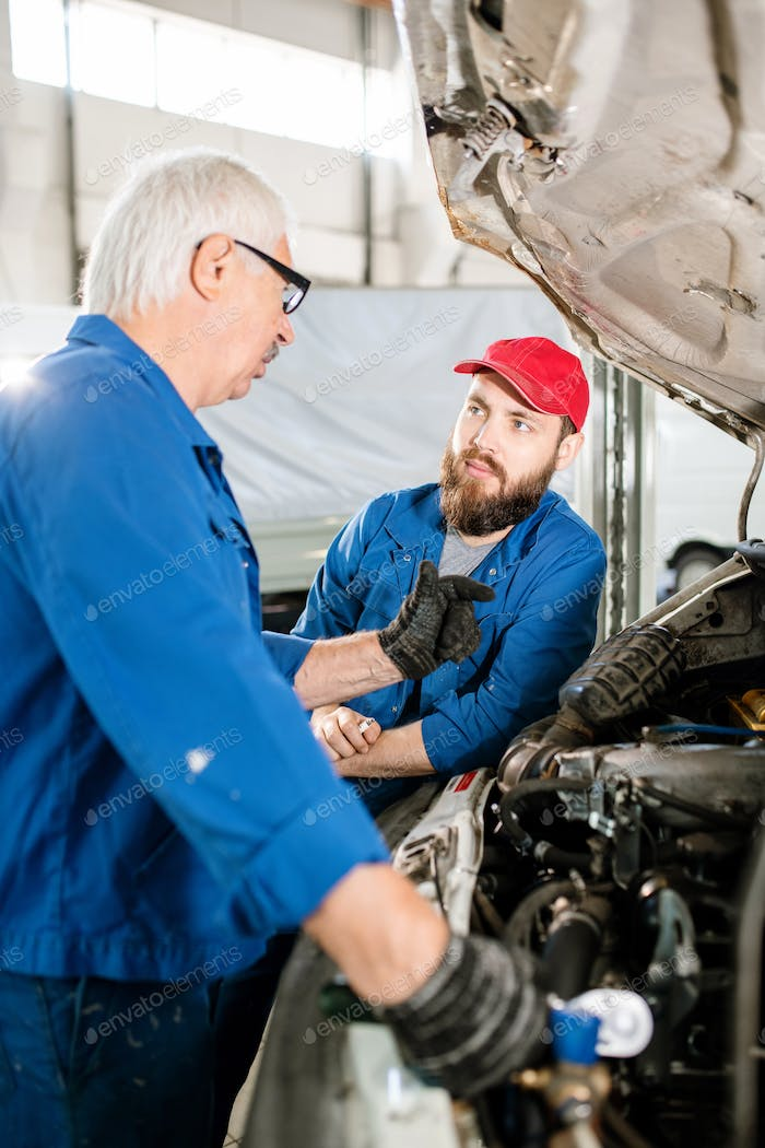 Experienced worker explaining his young colleague how to maintain vehicles