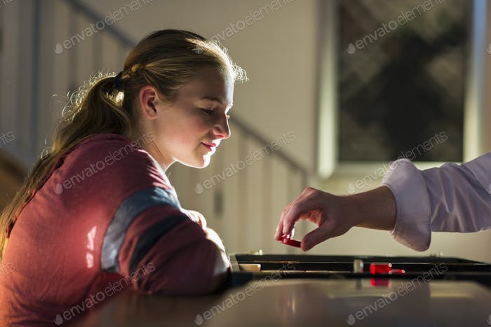 profile of 13 year old girl at sunset playing board game