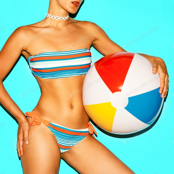 Tanned model in a fashionable swimsuit and with a beach ball.