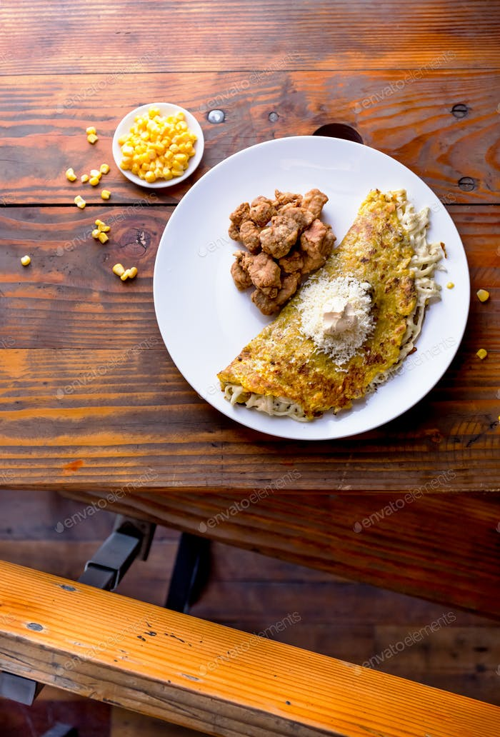 VENEZUELAN FOOD. Corn CACHAPA with cheese and fried pork - cochino frito