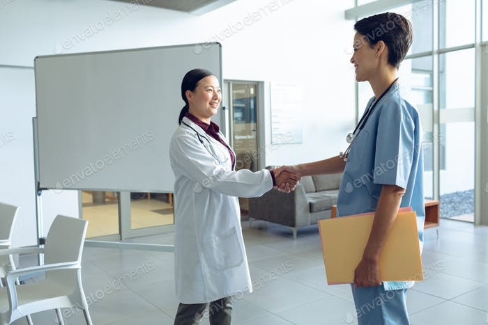 Side view of female Asian doctor shaking hands with female Caucasian nurse in the hospital