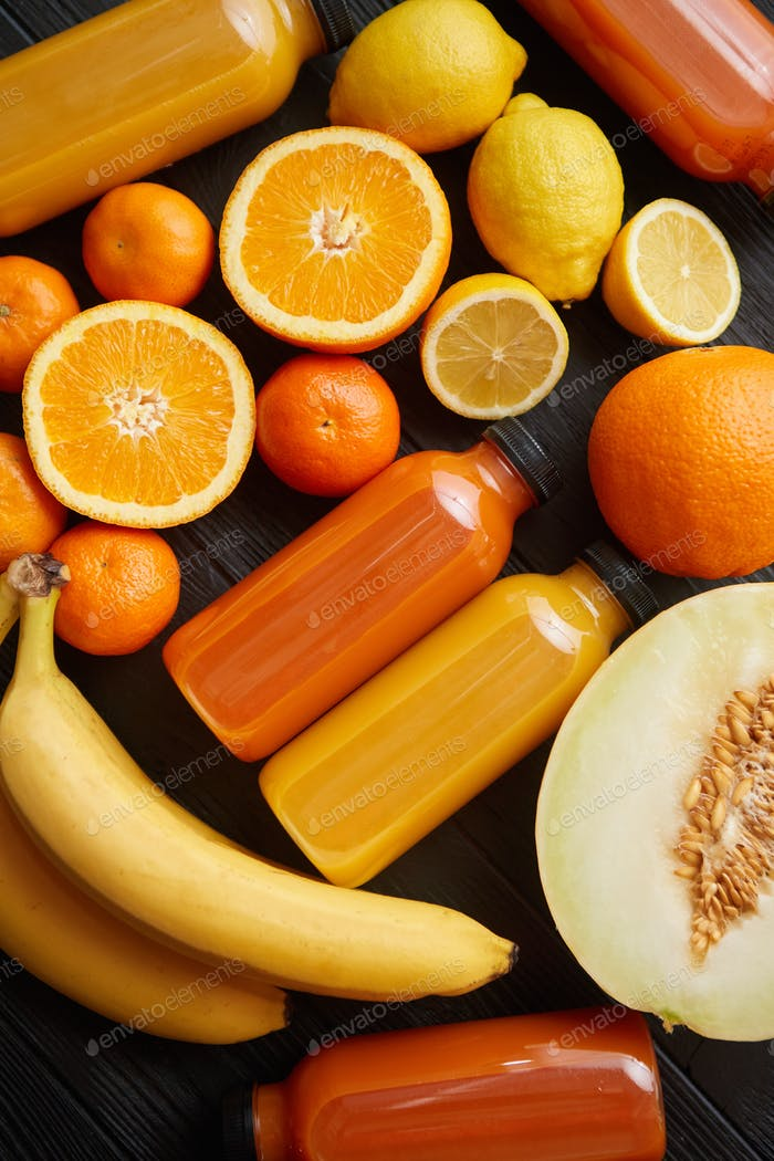 Mix of orange and yellow colored fruits and juices on black wooden background