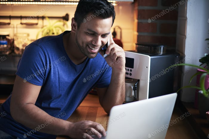 Glücklicher Mann im Gespräch mit dem Handy und mit dem Laptop