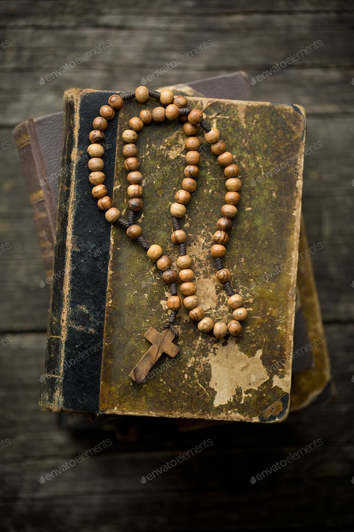 vintage rosary beads on old book