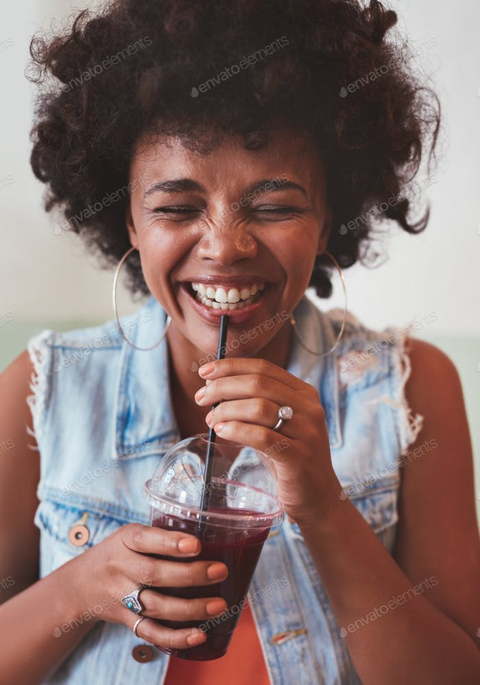 Happy young woman enjoying fresh fruit juice