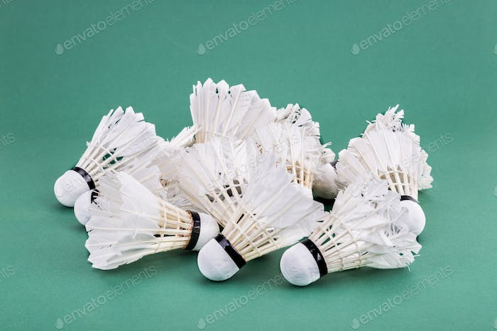Heaps of used and worned out badminton shuttlecock on green cour