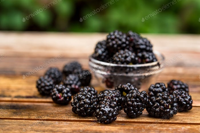 Fresh ripe blackberries in bowl on wooden table