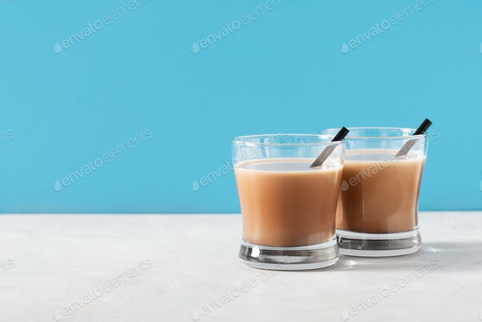 Chocolate drink in glass on blue background