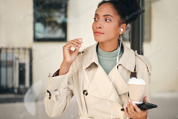 African American girl in stylish trench coat with and cellphone thoughtfully waiting bus at bus stop