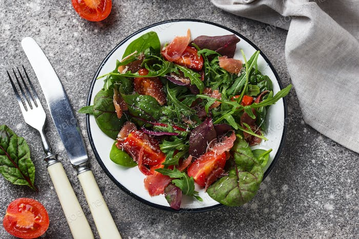 Healthy salad with prosciutto and tomato