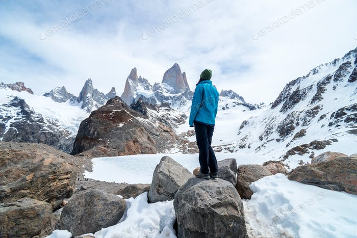 A hiker woman with a blue jacket on the base of Fitz Roy Mountain in Patagonia, Argentina