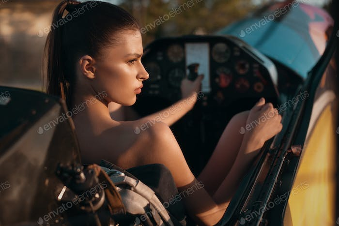Fashion pilot girl in a cabin of propeller plane during sunset