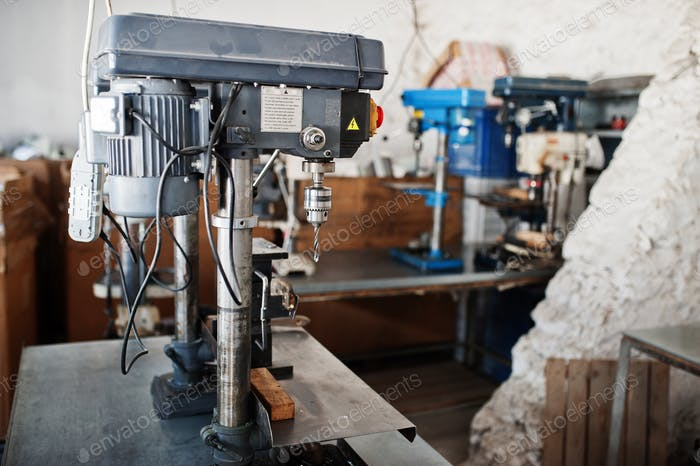 Metalwork tool drills at industrial factory.