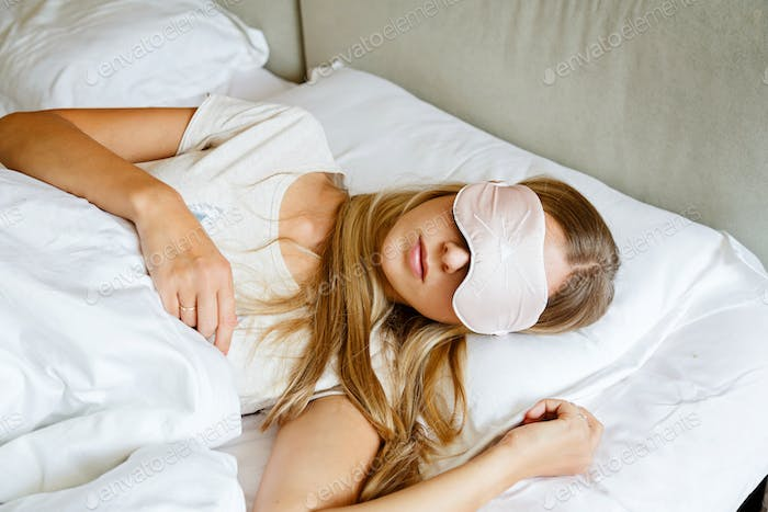 Young Caucasian Woman With Blonde Hair And Blindfold Sleeping in Bed