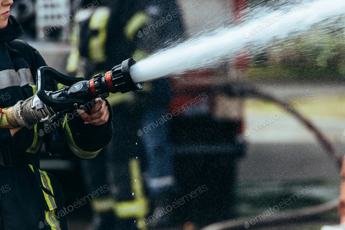 partial view of firefighter with water hose extinguishing fire on street