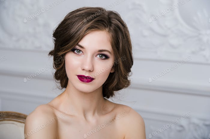 Portrait of beautiful woman with red lips at luxury interior room
