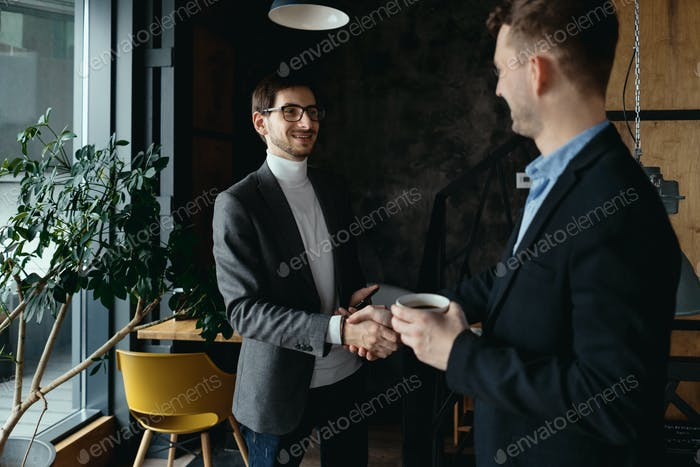 Two young businessmen greeting each other, shaking hand