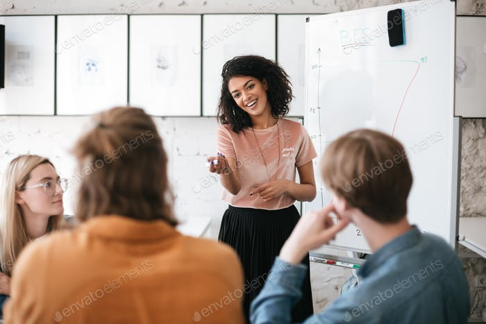 Young smiling business woman giving presentation to coworkers
