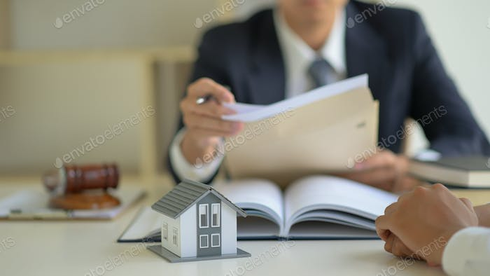 The lawyer is consulting clients about the house purchase contract.