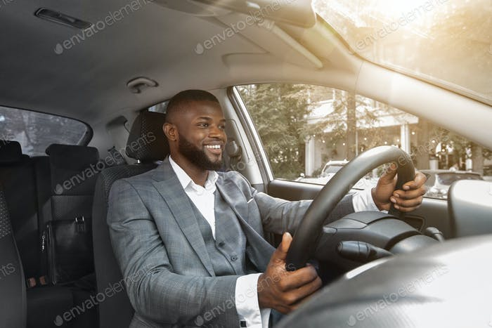 Positive african american businessman driving car, sun flare
