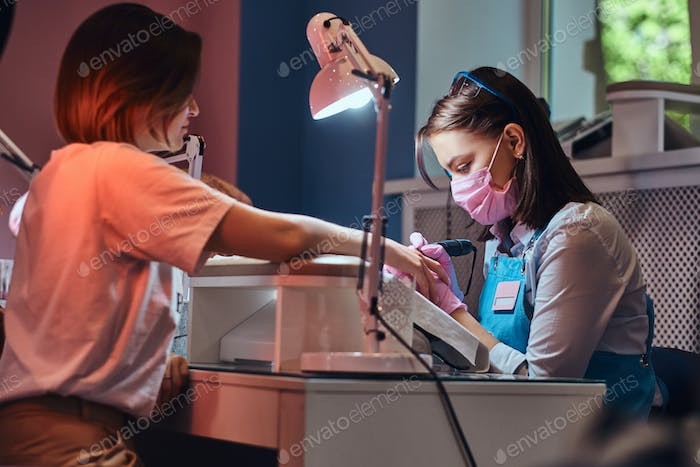 Young attractive manicurist is doing nail care for another woman