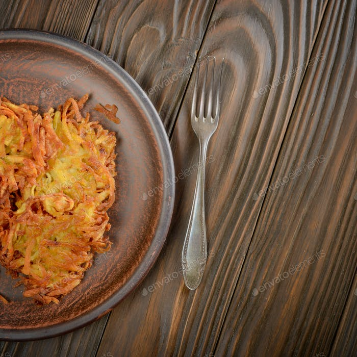 Top view of fresh homemade tasty potato pancakes in clay dish on
