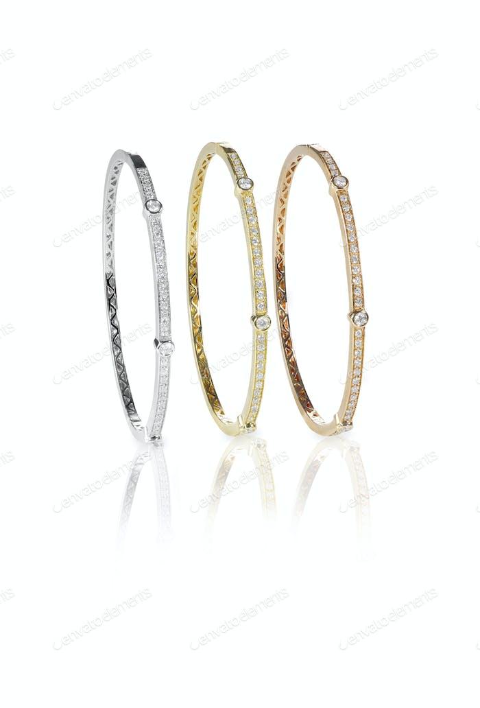 Set of three colored gold diamond bangle bracelets standing upright