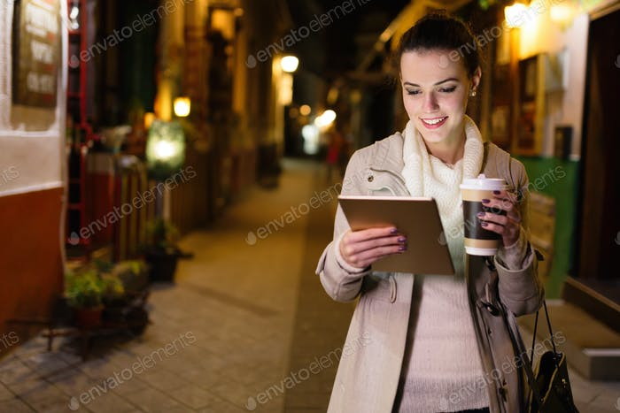 Attractive young woman using tablet and drinking coffee