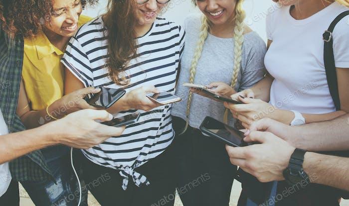 Junge erwachsene Freunde mit Smartphones zusammen im Freien Jugend cu