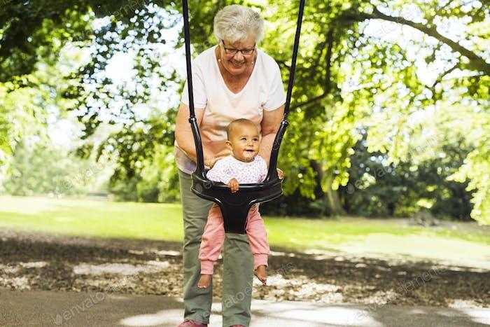 Grandmother swinging granddaughter (6-11 months)