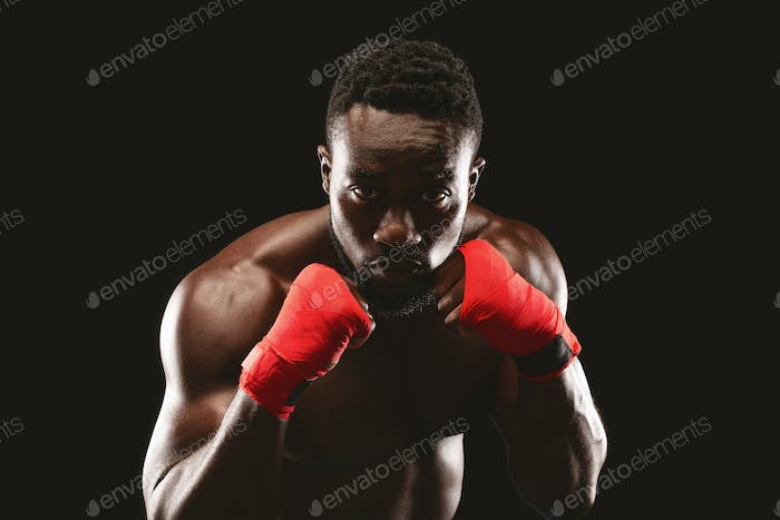 Professional fighter in boxing stance posing over black studio background