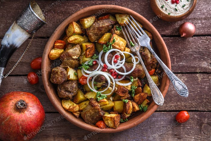 Große Keramikplatte mit gebratenem Fleisch und Kartoffeln mit Zwiebel und Wein.