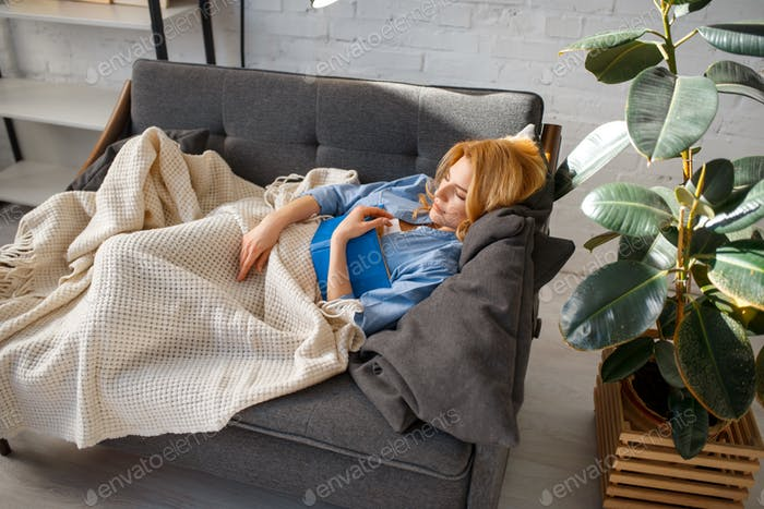 Young woman with book fell asleep on cozy couch