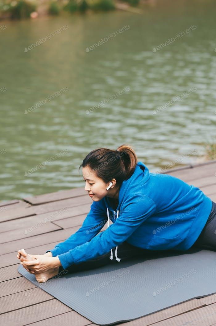 Young Asian woman doing yoga outdoors