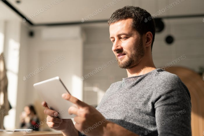 Casual young man with digital tablet communicating through video-chat