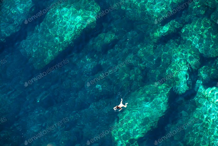 Drone view of a woman snorkeling in the sea