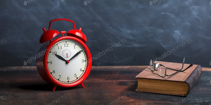 Red alarm clock, old books and reading glasses on a wooden table, black board background.