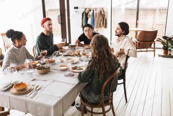 Young international friends sitting at the table full of food dreamily talking to each other