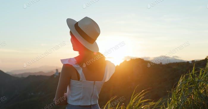 Frau genießen den Sonnenuntergang Blick auf die Berge