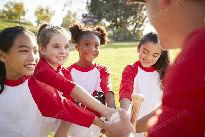 Schoolgirl baseball team in a team huddle with their coach
