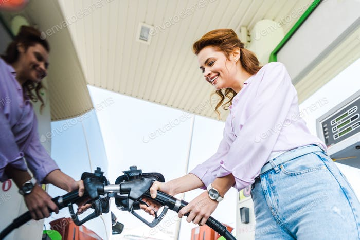 low angle view of happy woman holding fuel pump while refueling car with benzine