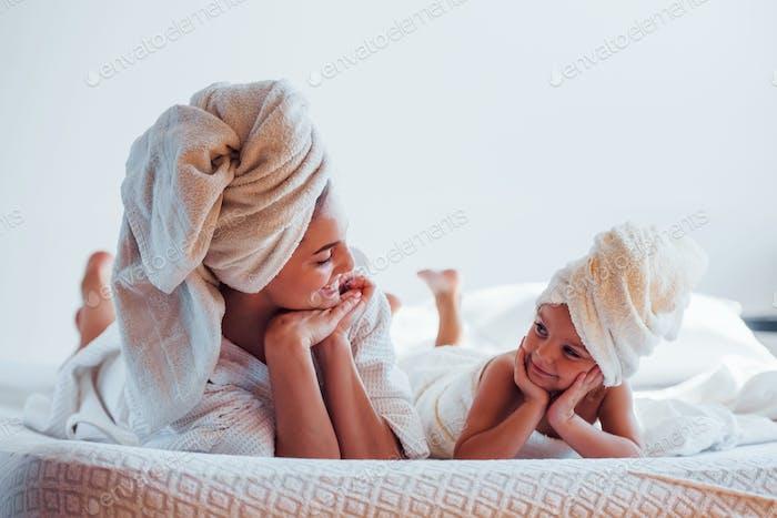 Лежа на белой кровати вместе. Молодая мать с дочерью имеют день красоты в помещении в комнате