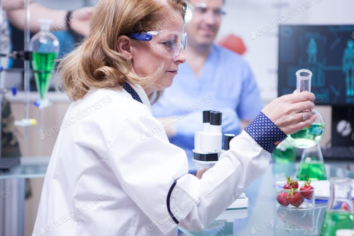 Side view of female scientist holding a test tube with green solution